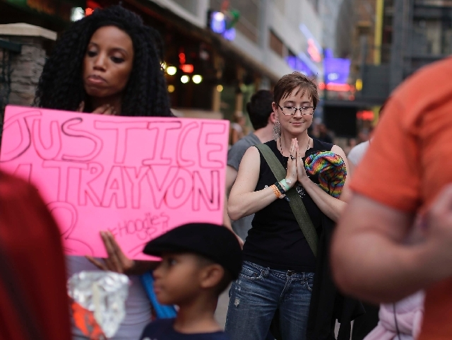 """Demonstrator Tiffany Stoddard, right, pauses for a moment of silence before participating in a ,""""Justice for Trayvon"""" march, Tuesday, July 16 near Las Vegas. Following George Zimmerman's Florida a ..."""