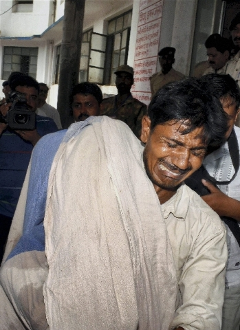 An Indian man cries while carrying the body of his daughter who died after eating a free school lunch at a hospital in Patna, India, Wednesday.