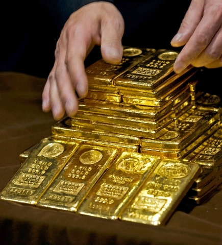 In an Oct. 17, 2011, file photo a staff member displays gold bullion bars during a news conference at the Chinese Gold and Silver Exchange Society in Hong Kong. A new study based on observations f ...