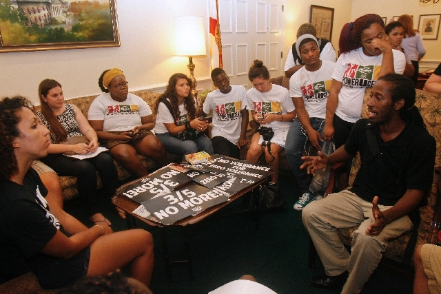 At right, Dream Defender member Travis Roberts tells other protestors about a time when he was racially profiled by law enforcement officers Wednesday inside Florida Gov. Rick Scott's office in th ...