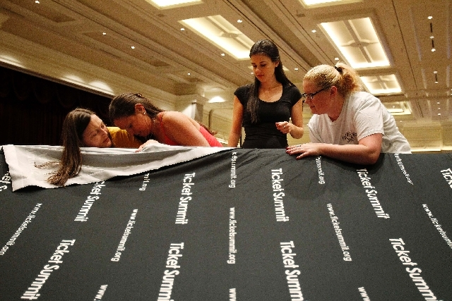 From left, Angie Grant, Sara Lomasky, Nichole Marsh and Sarah McComb on Tuesday prepare a backdrop for a booth at The Ticket Summit at Bellagio in Las Vegas.