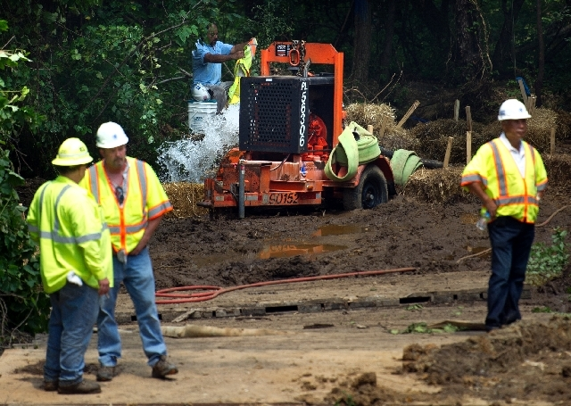 Washington Suburban Sanitary Commission workers pump water from a defective 4-1/2 water main in District Heights, Md., Wednesday, July 17, 2013. Officials say at least 200,000 residents could temp ...