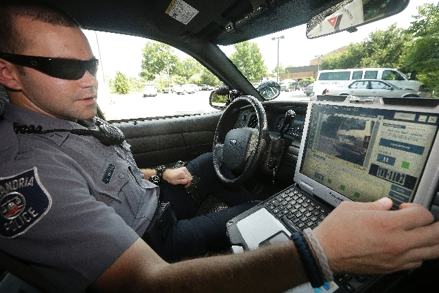 Officer Dennis Vafier, of the Alexandria Police Department, uses a laptop in his squad car to scan vehicle license plates during his patrols, Tuesday in Alexandria, Va. Local police departments ac ...
