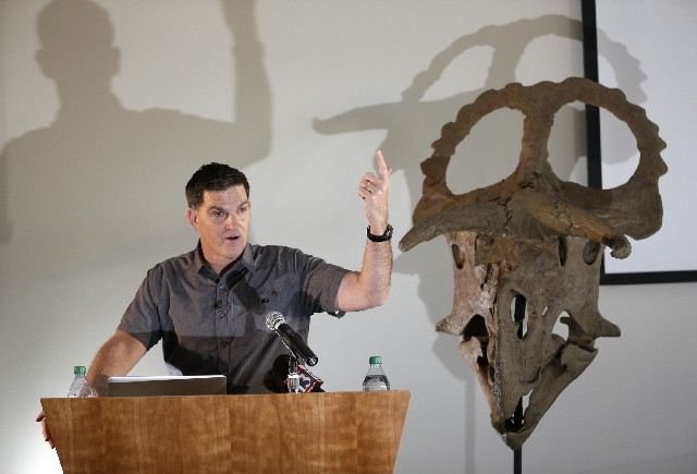 """Dinosaur paleontologist Scott Sampson,makes remarks as he stands next to a reconstruction of a """"Nasutoceratops titusi"""" during a news conference at the Natural History Museum of Utah Wednesday."""