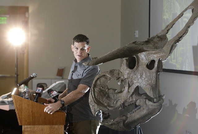 """Dinosaur paleontologist Scott Sampson, is shown making remarks as he stands next to a reconstruction of a """"Nasutoceratops titusi"""" during a news conference at the Natural History Museum of Utah Wed ..."""