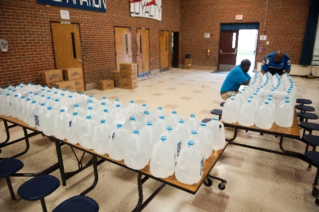 A worker waits to distribute one-gallon jugs of water at Friendly High School, main in Fort Washington, Md., Wednesday, July 17, 2013. for residents of Prince Georges County who are affected by th ...