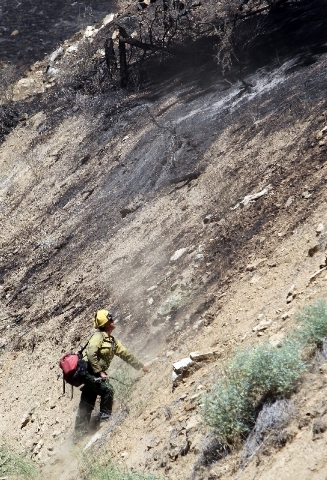 Firefighters battle the Pine Creek Fire northeast of Boise, Idaho, on Wednesday afternoon in Boise County along Grimes Creek Road. Lightning ignited at least eight new fires on the Boise National  ...