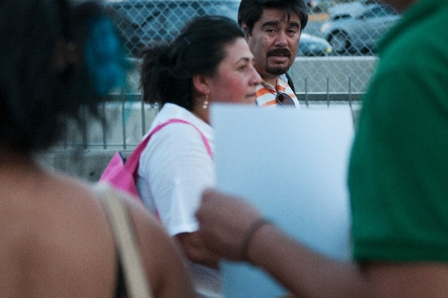 Passers-by watch demonstrators hold signs in protest of a border militarization at an immigration rally on Wednesday in front of the New York-New York in Las Vegas.