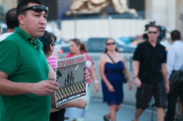 Martin Martinez holds a sign in protest of a border militarization at an immigration rally on Wednesday in front of the New York-New York in Las Vegas.