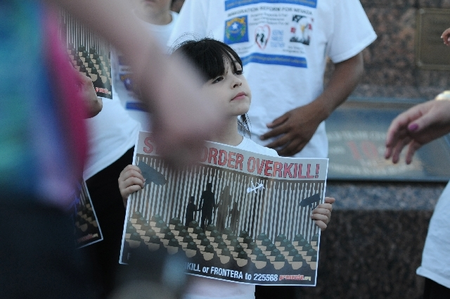 Mia Williams, 4, holds a sign in protest of a border militarization at an immigration rally she attended with her mother Sandy Julian on Wednesday in front of the New York-New York in Las Vegas.