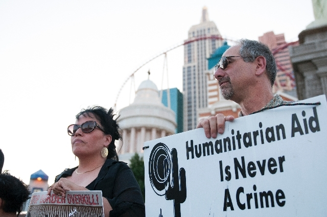 Rosa Mendoza, right, holds a sign in protest of a border militarization at an immigration rally on Wednesday in front of the New York-New York in Las Vegas.