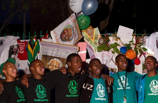 A group of students sing happy birthday for former South African President Nelson Mandela Thursday, outside the hospital where Mandela is being treated in Pretoria, South Afric. South Africa celeb ...