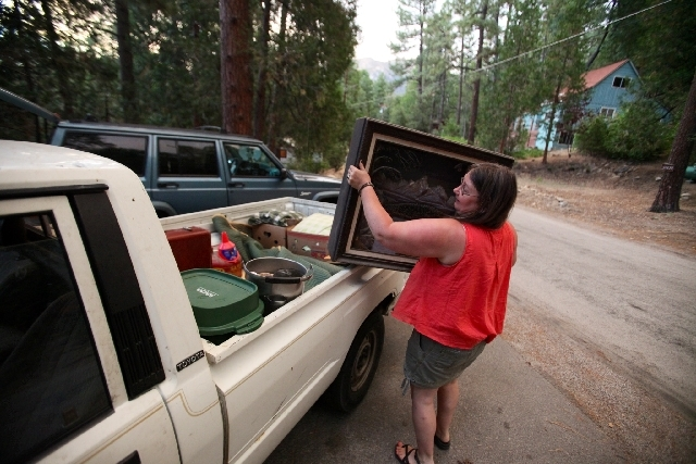 Deidra Wood evacuates her home with 3 dogs, one cat and a fish ahead of the approaching Mountain Fire in Idyllwild Calif., Wednesday, July 17, 2013. Some 6,000 residents and visitors in Idyllwild  ...