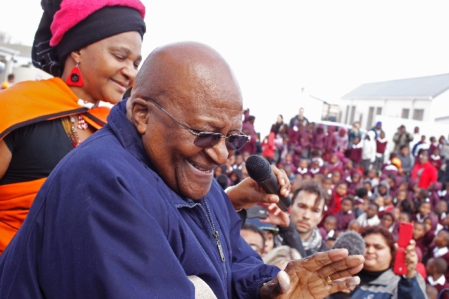 Bishop Desmond Tutu, center, celebrates former South African President Nelson Mandela's birthday Thursday at a school in Cape Town, South Africa.