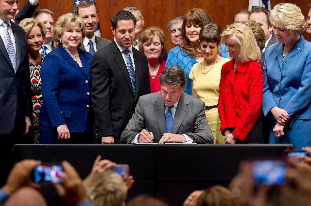 Surrounded by legislators, Governor Rick Perry signs HB2 in the Capitol Extension Auditorium on Thursday.