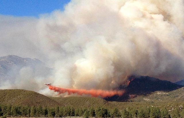 In this photo made Wednesday, July 17, 2013, and released by the U.S. Forest Service, a DC-10 drops fire retardant along an edge of the Mountain Fire near Lake Hemet, Calif.