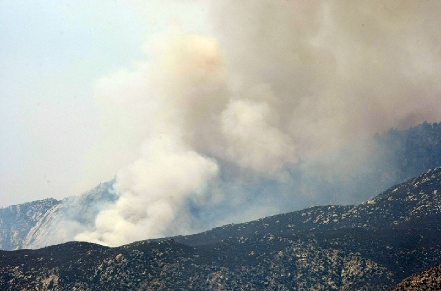 Smoke rises over the ridges above Palm Springs, Calif. as the Mountain Fire advances along the San Jacinto Mountain range, Thursday.