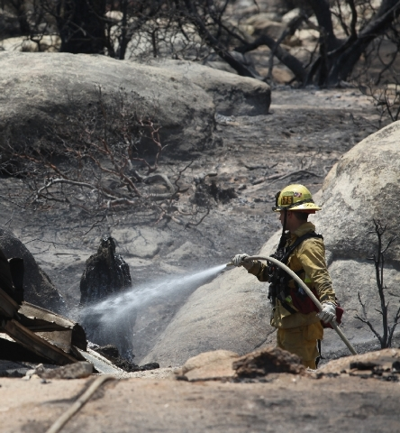 A Rancho Cucamonga firefighter mops up an area in Pine Springs Ranch in Mountain Center, Calif. Thursday as crews continue to battle the Mountain Fire.