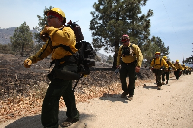 Members of the Mountaineer Fire Crews from Northern California start their hike near Pine Springs Ranch in Mountain Center, Calif. to fight the Mountain Fire Thursday.