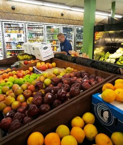 Simoon Boles arranges produce at the new White Cross Market on Las Vegas Boulevard on Friday. The market will open to the public Saturday.