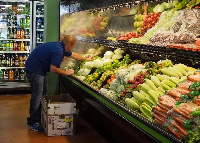 Simoon Boles arranges produce at the new White Cross Market on Las Vegas Boulevard on Friday. The market will open to the public Saturday