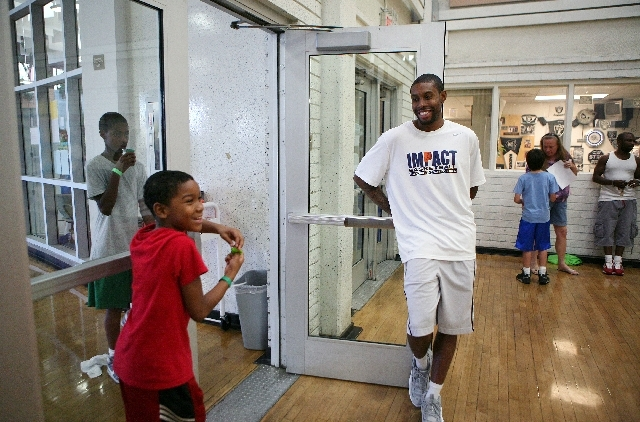 Ryan Ramirez, 10, left, laughs with Indiana Pacers guard C.J. Watson during the Hoops for Hope basketball camp at Doolittle Community Center. Watson's Quiet Storm foundation conducts the youth clinic.