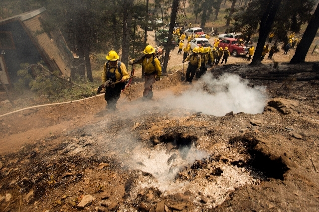 Firefighters head back to fight the Carpenter 1 Fire after a break at Mount Charleston's Rainbow subdivision on July 9. More than 800 personnel worked to fight the blaze in the Spring Mountains Na ...
