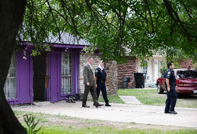 Authorities investigate a home Friday in Houston where police say four homeless men were found in deplorable conditions