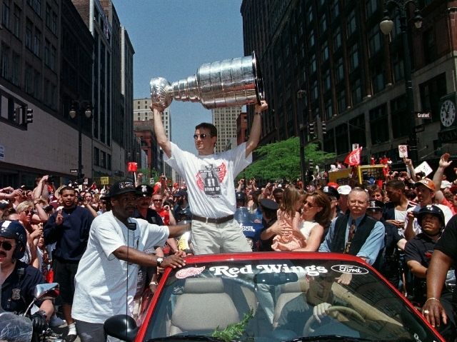 In this June 10, 1997 file photo, Detroit Red Wings captain Steve Yzerman holds up a trophy as he acknowledges the crowd with his family during the Stanley Cup parade in Detroit to honor the NHL c ...