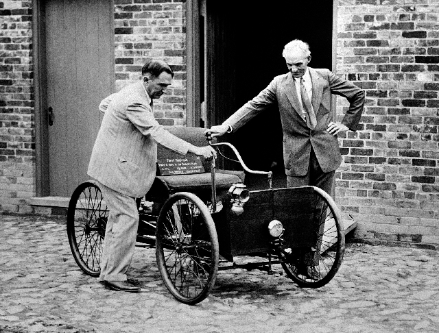 In this Dec. 10, 1936 file photo, Henry Ford, right, stands with his first car built in 1892, assembled in the brick barn in the background in Detroit. At left is James Bishop.