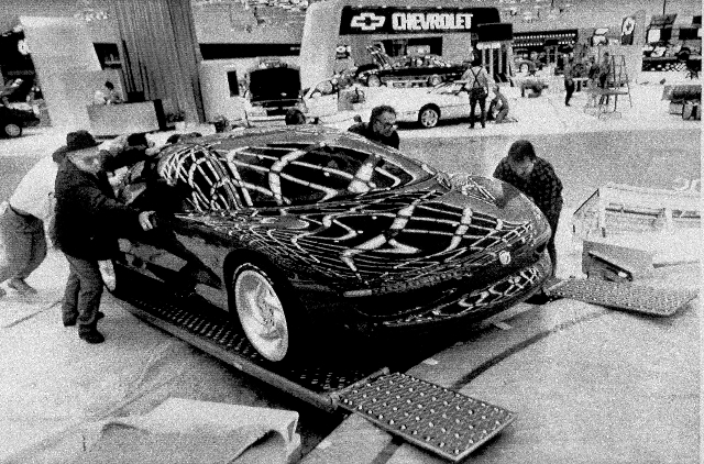 Workers roll a Mercury Cyclone concept car up a ramp into its display area as work continues at Cobo Center in Detroit for the North American International Auto Show, Jan. 2, 1990.