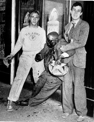 In this June 21, 1943 file photo, two white youths help a black man to his feet after he was badly beaten in street fighting during race riots in Detroit.