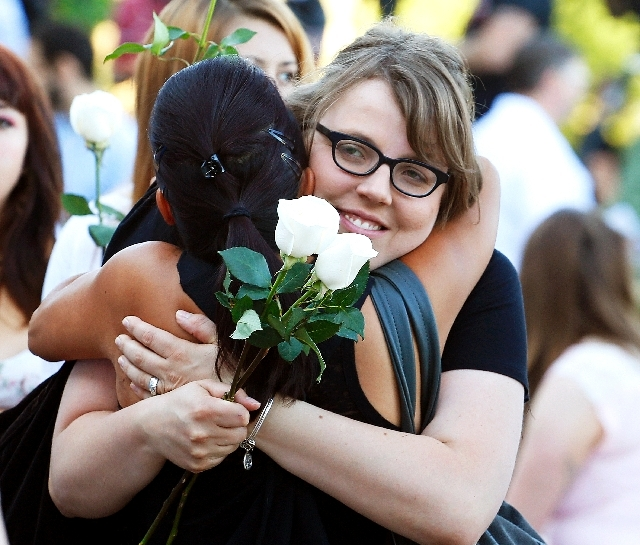 Megan Sullivan, right, the sister of Alex Sullivan who was killed last year in the Aurora movie theater shooting, is hugged by Linda Klosowski at a memorial service in Aurora, Colo., on Saturday.  ...