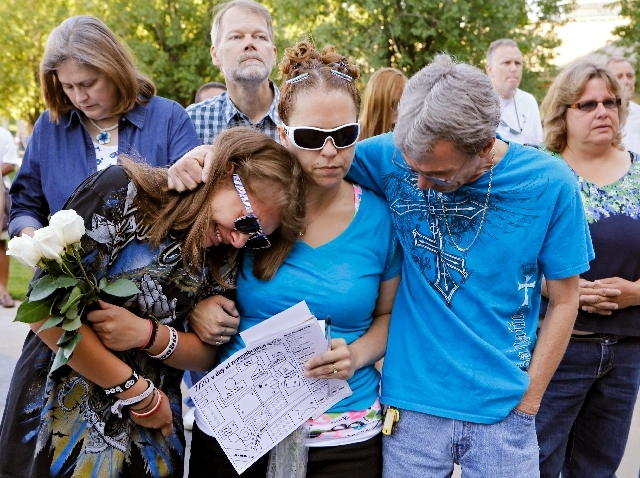 Jasmine Christman, left, is comforted by her mother Yulanda Vega Jordan, center, and father Jack Jordan during a memorial service in Aurora, Colo., on Saturday. Coloradans marked the one-year anni ...