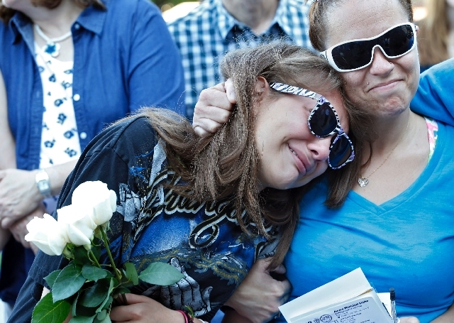 Jasmine Christman, left, is comforted by her mother Yulanda Vega Jordan during a memorial service for the victims of the Aurora theater shooting on the anniversary of the tragedy in Aurora, Colo., ...