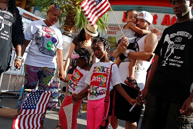 Six-year-old MiAsia Moore, center left, holds hands with  7-year-old MiKym Moore, center right, and others during a rally in support of Justice for Trayvon Martin in downtown Las Vegas Saturday.
