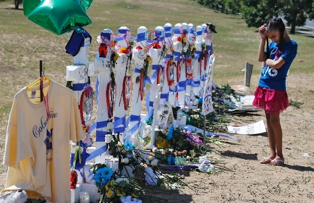 Amilya Scott, 9, visits a temporary memorial for the victims of the Aurora theater shooting in Aurora, Colo., on Saturday.