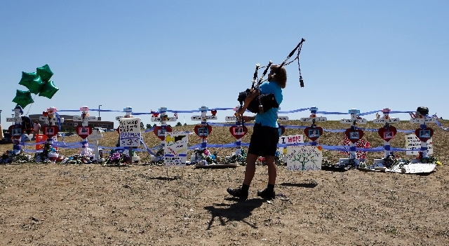 Becky Nelson plays the bag pipes at a temporary memorial for the victims of the movie theater shooting in Aurora, Colo., on Saturday. Coloradans marked the one-year anniversary of the Aurora movie ...