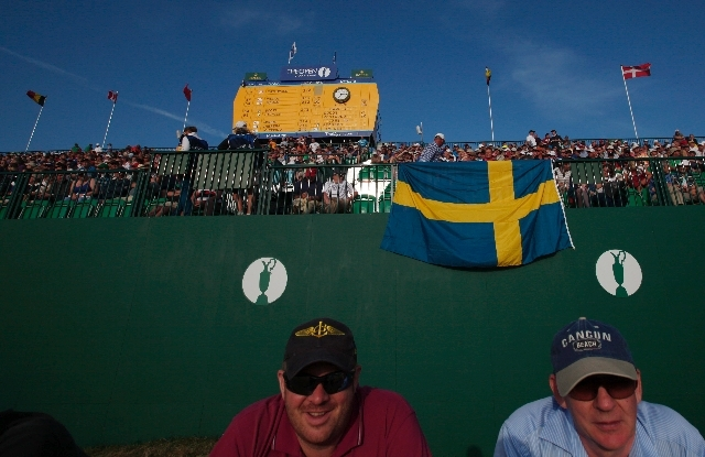 Two spectators watch the 18th hole of the British Open from under a Swedish Flag.