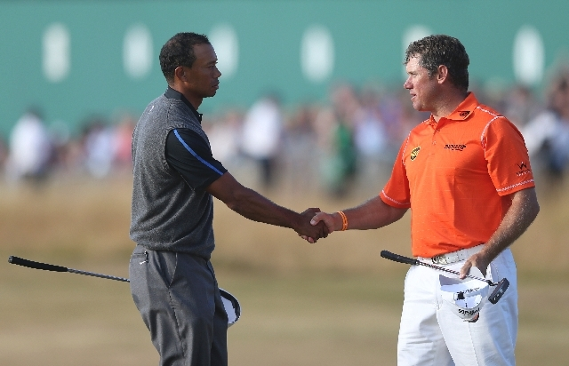 Tiger Woods of the United States, left, shakes hands with Lee Westwood of England on the 18th green after their third round of the British Open Golf Championship at Muirfield, Scotland, Saturday J ...