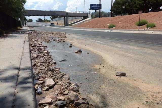 Rocks and debris litter the road below the railroad bridge that crosses Owens Avenue just east of Interstate 15 in Las Vegas on Saturday. Friday night's storm sent a flash flood down the road leav ...