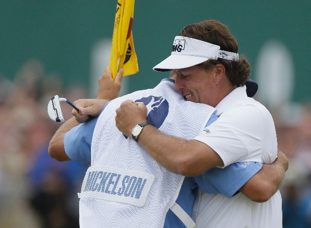 Phil Mickelson of the United States celebrates after his final putt on the 18th green with his caddie Jim Mackay during the final round of the British Open Golf Championship at Muirfield, Scotland ...