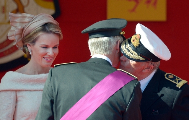 Belgium's King Philippe, center, is kissed by his father King Albert II, right, as Queen Mathilde looks on during a military parade in Brussels on Sunday.
