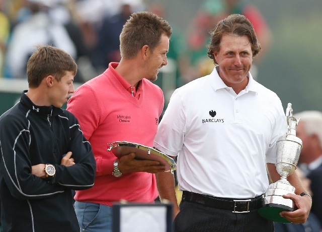 Phil Mickelson of the United States holds the Claret Jug trophy after winning the British Open Golf Championship with runner up Henrik Stenson of Sweden, center, and leading amateur Matthew Fitzpa ...