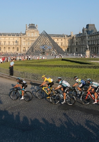 The pack, with Christopher Froome of Britain, wearing the overall leader's yellow jersey, center, rides through the courtyard of the Louvre museum, during the 21st and last stage of the 100th edit ...