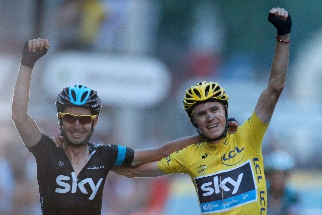 2013 Tour de France cycling race winner Christopher Froome of Britain, wearing the overall leader's yellow jersey, crosses the finish line with a teammate in the last stage of the 100th edition of ...