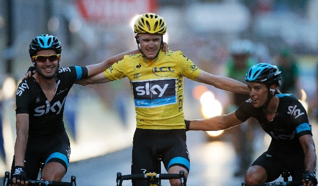 Team Sky with 2013 Tour de France cycling race winner Christopher Froome of Britain, wearing the overall leader's yellow jersey, crosses the finish line of the 21st and last stage of the 100th edi ...