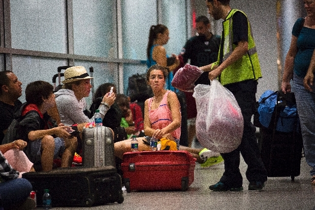 Stranded passengers are handed blankets while they wait at LaGuardia Airport as multiple flights were canceled after a Southwest Airlines 737 plane's nose gear collapsed during a landing, Monday,  ...