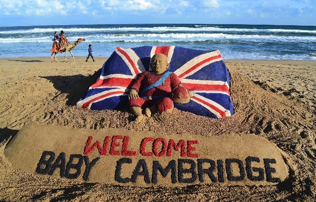 Tourists ride a camel past a sand sculpture created by sand artist Sudarshan Pattnaik to celebrate the birth of the Prince of Cambridge, the son of Britain's Prince William and Kate, Duchess of Ca ...