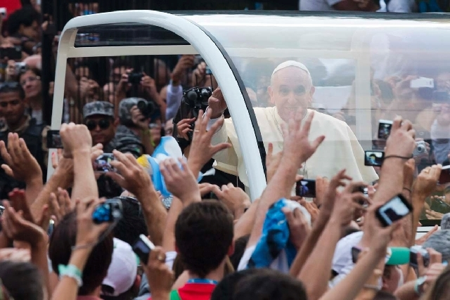 People reach out to Pope Francis as he rides in a popemobile through Rio de Janeiro, Brazil, on Monday. Pope Francis returned to his home continent for the first time as pontiff, embarking on a se ...